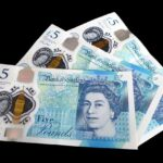 Three £5 notes on a black background