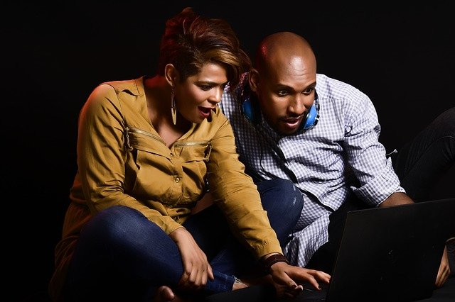 Man and a woman sat on floor looking at a laptop screen, suggesting shock or surprise