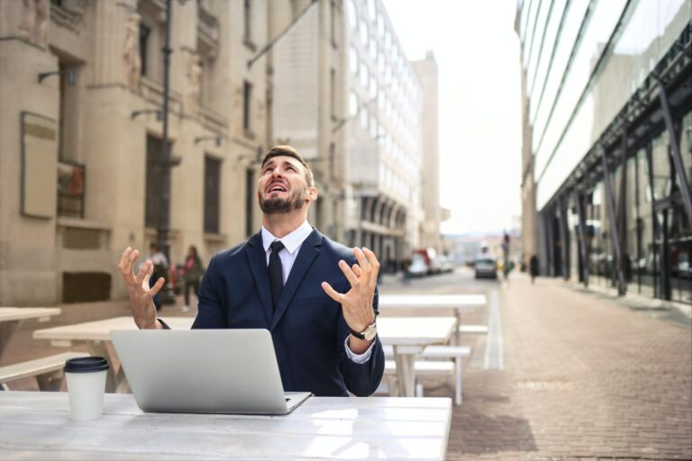 Man in a blue suit sat in front of a laptop at a picnic table outside, hands raised, and looking at the sky, suggesting anger, annoyance or frustration