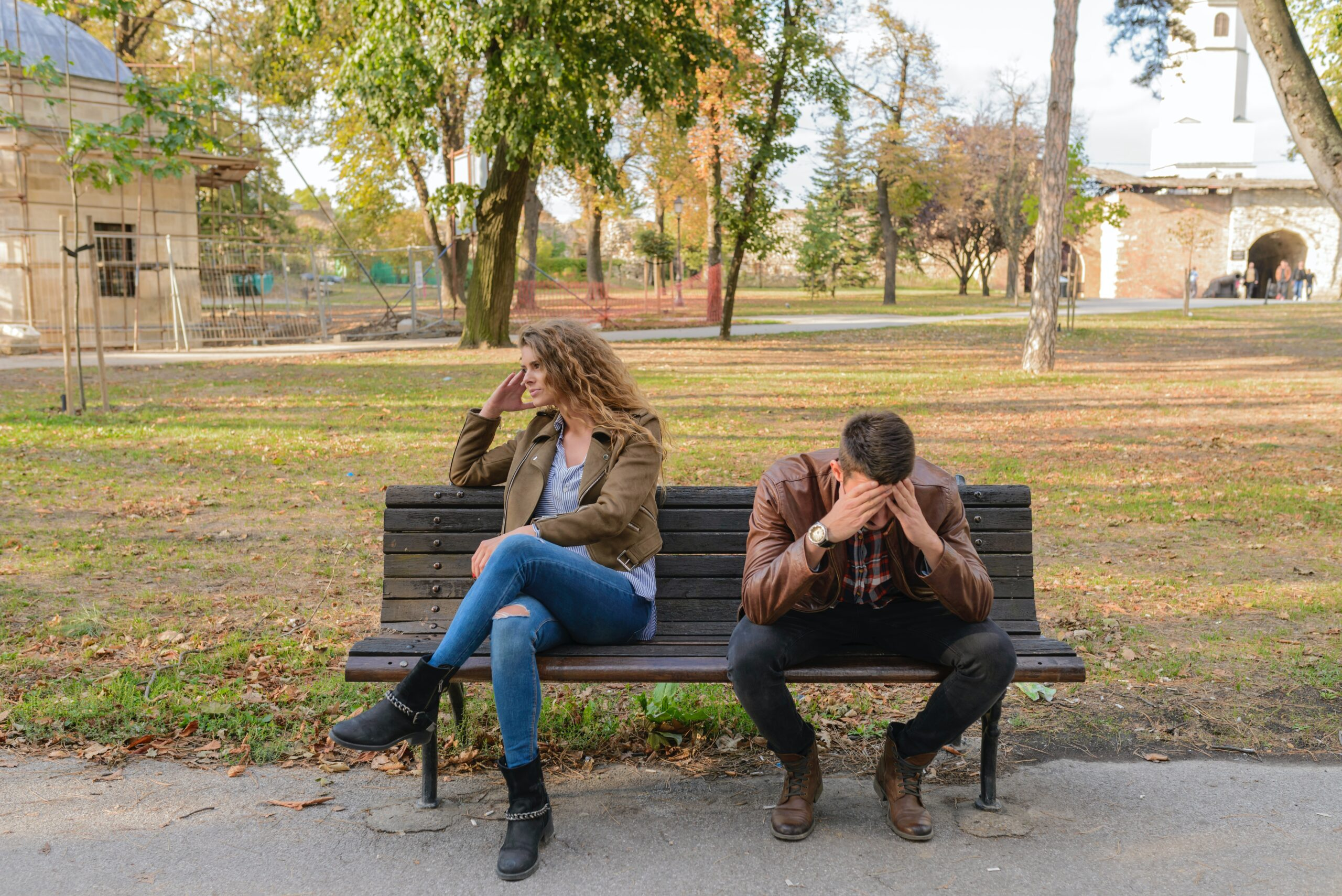 Woman and man sat apart on a bench, suggesting a falling out