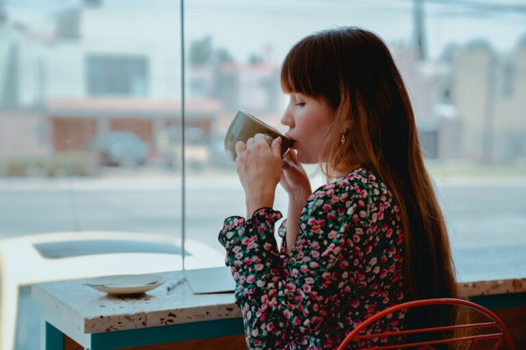 Mid-20s woman with long brown hair, and her eyes closed, in a coffee shop, wearing a flowery top, drinking from a green cup with two hands, suggesting a really enjoyable cup of coffee or hot chocolate