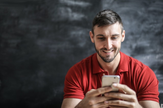 Mid-20s bearded man wearing a red polo shirt, holding his phone and smiling, sitting in front of what might be a black board