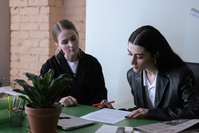 Two mid-20s women in an office sitting a desk looking over a printed out document, suggesting working together, or another pair of eyes