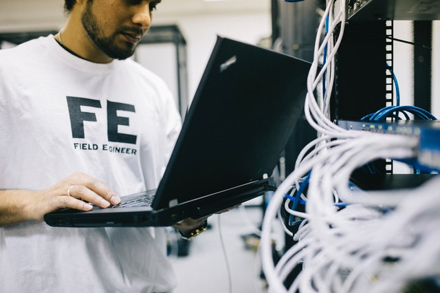 Field engineer holding a laptop next to what looks like lots of wires, suggesting either a telecoms engineer or a network engineer
