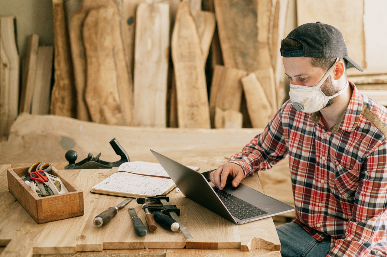 Man wearing a red checked shirt sat in front of pieces of wood, suggesting a table. He's wearing a woodworking mask, surrounded by bits of wood. He's looking at a laptop with several woodworking tools next to him, suggesting he might be looking at instructions, a pattern or blueprint