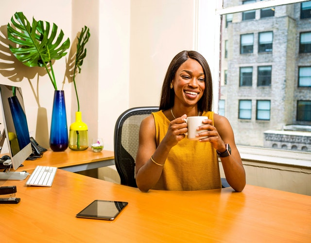 Woman of colour sat at a desk in an office, drinking a cup of coffee and smiling, suggesting she's taking a break from working. Her iPad is on her desk.