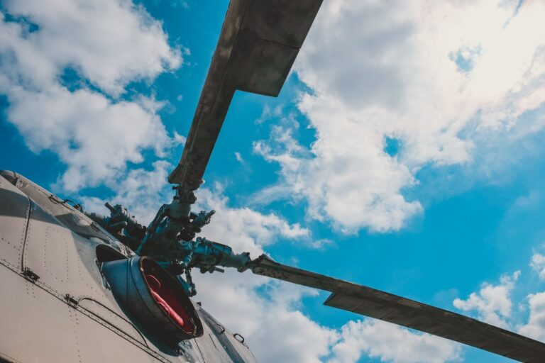 Helicopter rotors, taken from the ground looking up at a cloudy sky, suggesting flight
